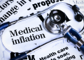 Stethoscope sits on newspaper headlines about medical inflation