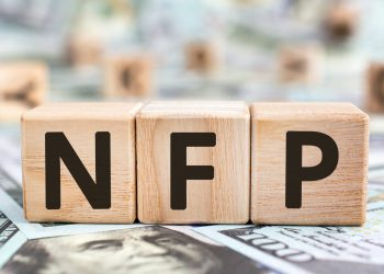 NFP - acronym from wooden blocks with letters, abbreviation NFP Nonfarm Payrolls key economic indicator or Natural Family Planning concept, random letters around, money background