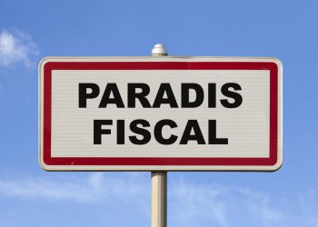 """A French entry city sign against a blue sky with written in the middle in French """"Paradis fiscal"""", meaning in English """"Tax haven""""."""