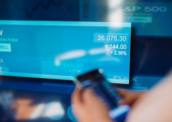 Woman trading stock with mobile app in front of stock exchange screen.