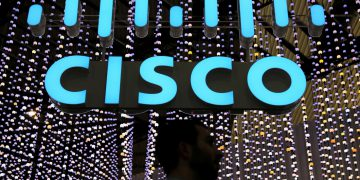 FILE PHOTO: A man passes under a Cisco logo at the Mobile World Congress in Barcelona, Spain February 25, 2019. REUTERS/Sergio Perez/File Photo    GLOBAL BUSINESS WEEK AHEAD